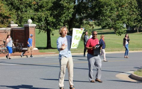 Hunter Potts (center) stands in the street, asking drivers to honk for climate change, while Teshome Molalenge (right) looks on with his tablet.