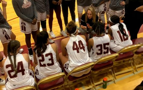Women's Basketball Head Coach Sarah Mathews gives her team a pep talk as they take the court to play the Bullets.
