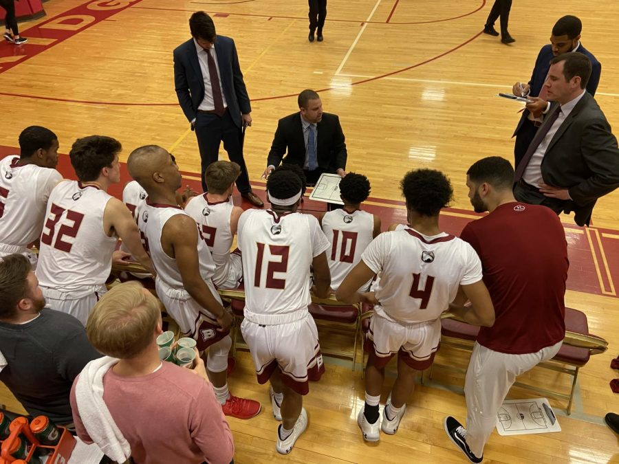 The men's basketball team huddles around their coach during their first time out in their game against Hampden-Sydney.