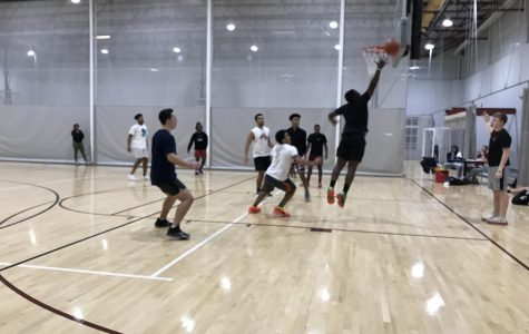 After a missed shot, a player attempts to jump up and rebound the ball off the backboard. Most players take a lot of pride in these intramural games as it gives them the opportunity to show off their skills in basketball.