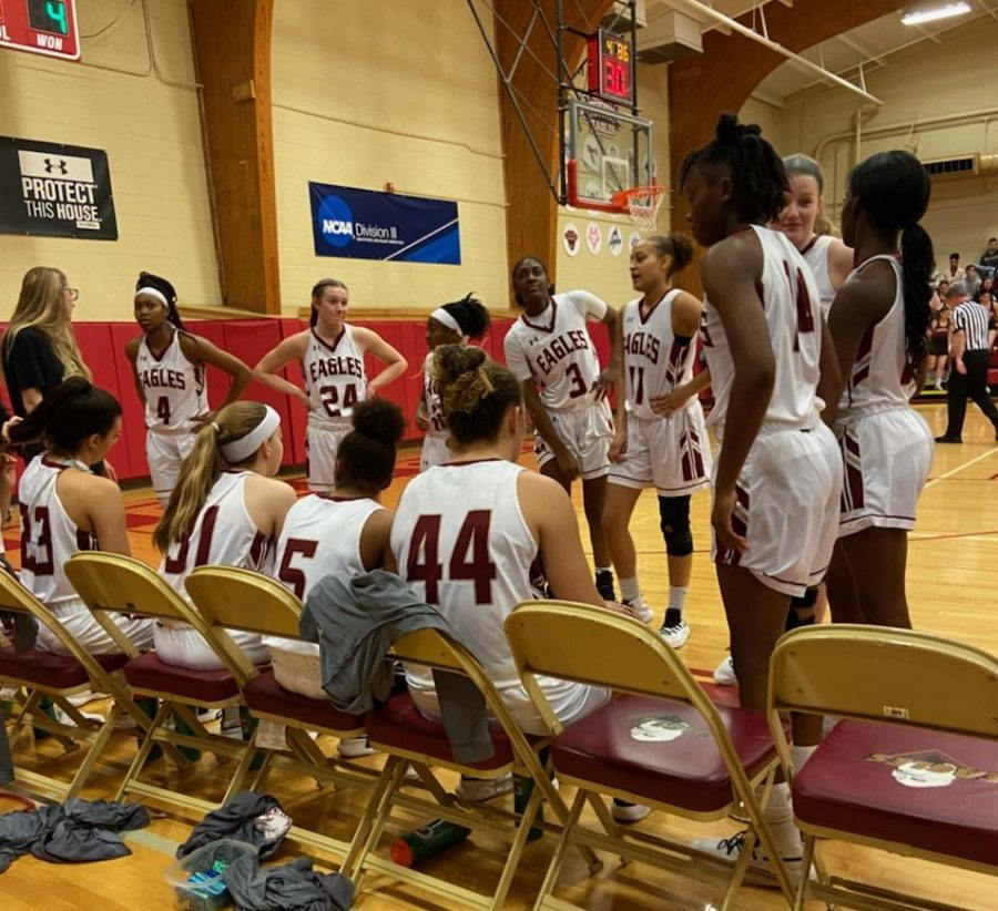 The women's basketball team huddles up to talk in the first timeout of their game against Eastern Mennonite University.