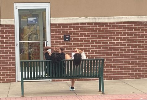 Showing two girls from a distance sitting on a bench